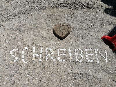 """Schriftzug """"Schreiben"""" im Sand"""