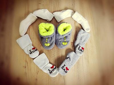 Babyschuhe in einem Herz aus Socken