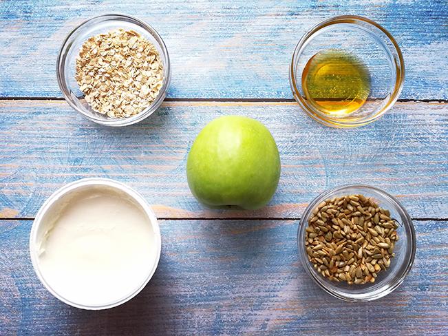 Joghurt, Apfel, Honig, Haferflocken und Sonnenblumenkerne